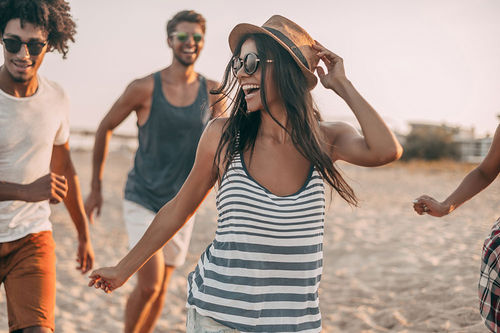 young woman smiling and running with her friends at the beach